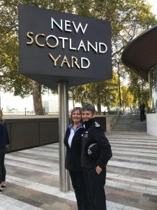 Two policewomen stand underneath the New Scotland Yard sign