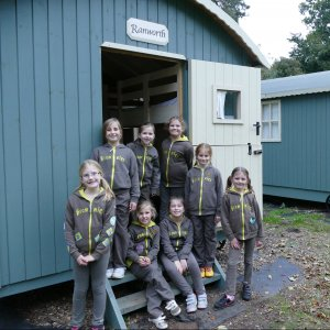 Group of eight Brownies in front of a shepherds hut