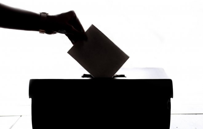 a silhouette of a ballot box and a voters hand