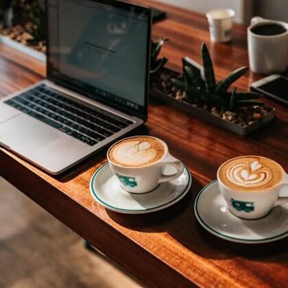 Two cups of coffee in front of a laptop