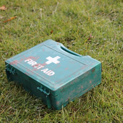 A muddy and well used first aid box on grass